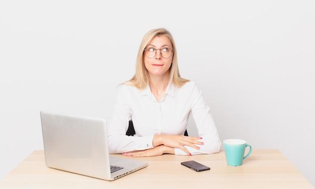 Blond ładna kobieta młoda blondynka wygląda na zdziwioną i zdezorientowaną i pracuje z laptopem