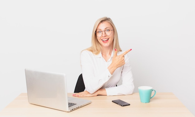 Blond ładna kobieta młoda blondynka wyglądająca na podekscytowaną i zdziwioną, wskazując na bok i pracująca z laptopem