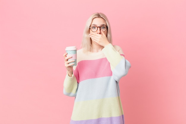 Blond ładna kobieta obejmujące usta rękami z szoku. koncepcja kawy