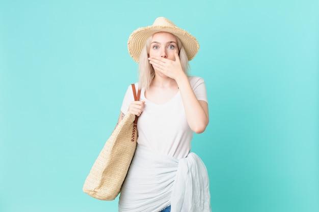 Blond ładna kobieta obejmujące usta rękami z szoku. koncepcja lato