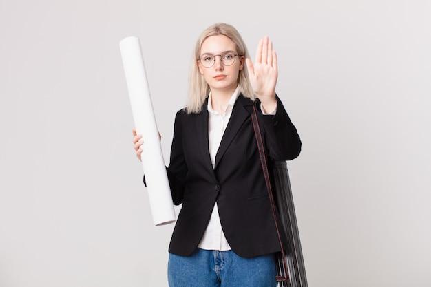Blond ładna kobieta patrząc poważne wyświetlono otwartej dłoni dokonywanie gest stop. koncepcja architekta