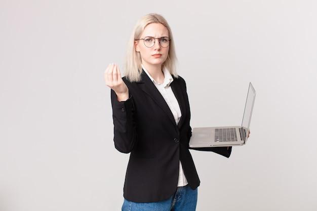 Blond ładna kobieta robi gest kaprysu lub pieniędzy, mówiąc, że masz zapłacić i trzymając laptopa