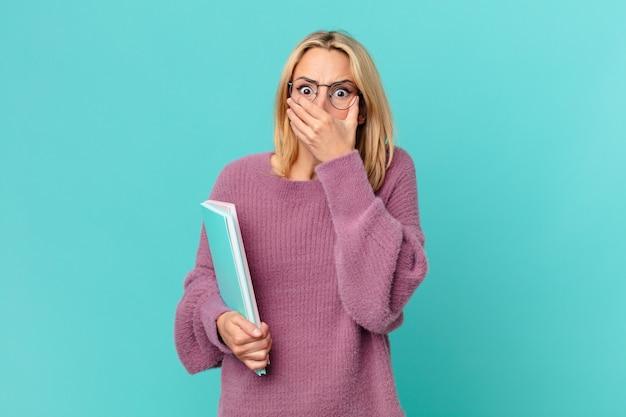 Blond ładna kobieta trzyma książki. koncepcja studenta