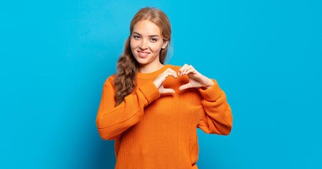 Blond ładna kobieta uśmiecha się i czuje się szczęśliwa, urocza, romantyczna i zakochana, tworząc kształt serca obiema rękami