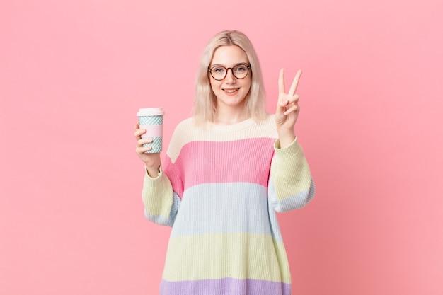 Blond ładna kobieta uśmiecha się i wygląda na szczęśliwą, gestykulując zwycięstwo lub pokój. koncepcja kawy