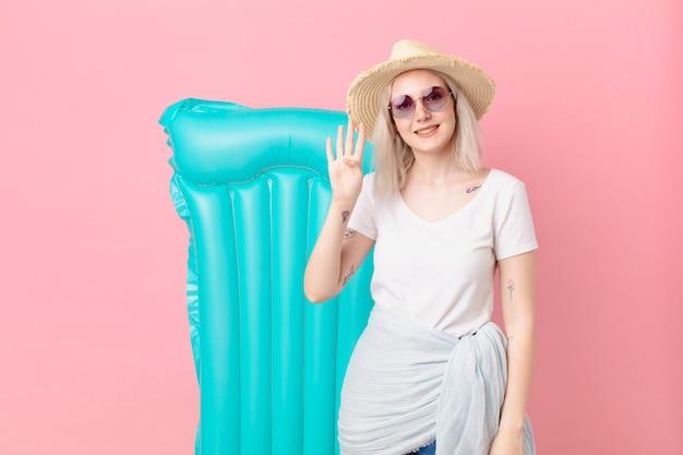 Blond ładna kobieta uśmiecha się i wygląda przyjaźnie, pokazując numer cztery. koncepcja lato