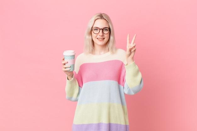 Blond ładna kobieta uśmiecha się i wygląda przyjaźnie, pokazując numer dwa. koncepcja kawy