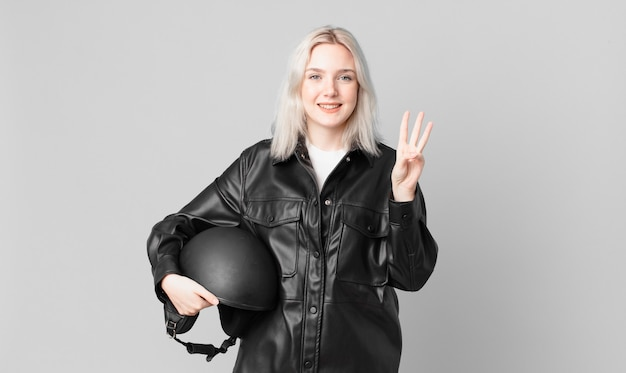 Blond ładna kobieta uśmiecha się i wygląda przyjaźnie, pokazując numer trzy. koncepcja motocyklisty