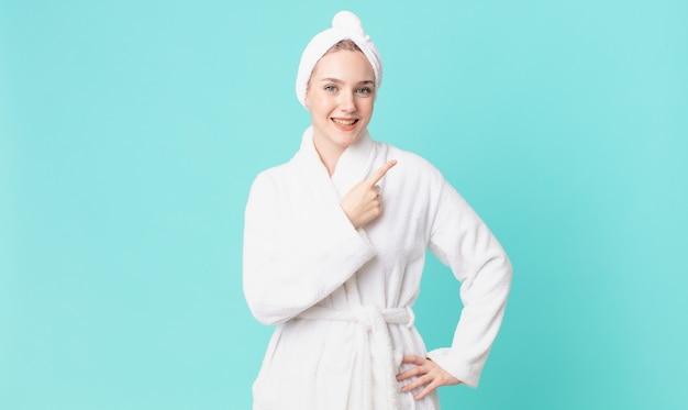 Blond ładna kobieta uśmiecha się radośnie, czuje się szczęśliwa, wskazuje na bok i ma na sobie szlafrok