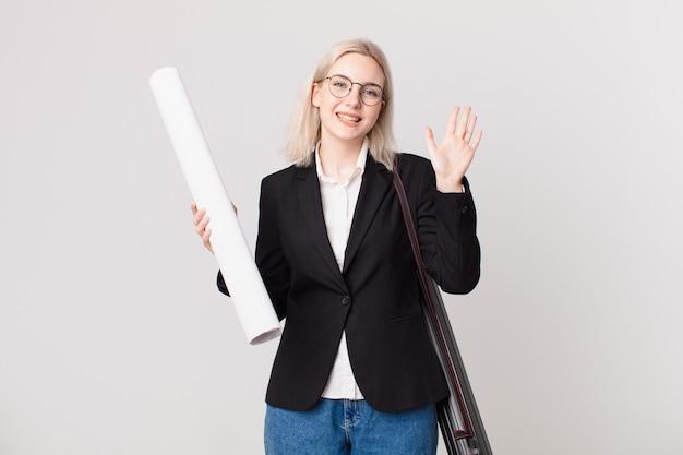 Blond ładna kobieta uśmiecha się radośnie, machając ręką, witając cię i pozdrawiając. koncepcja architekta