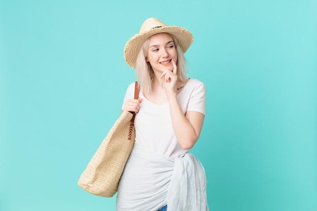Blond ładna kobieta uśmiecha się ze szczęśliwym, pewnym siebie wyrazem twarzy z ręką na brodzie. koncepcja lato
