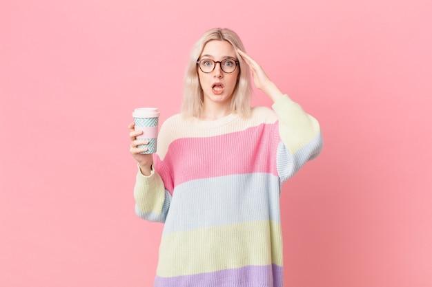 Blond ładna kobieta wygląda na szczęśliwą, zdumioną i zdziwioną. koncepcja kawy