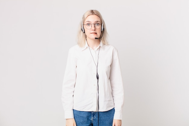 Blond ładna kobieta wygląda na zdziwioną i zdezorientowaną koncepcję telemarketingu