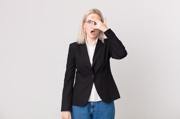 Blond ładna kobieta wygląda na zszokowaną, przestraszoną lub przerażoną, zakrywając twarz ręką. pomysł na biznes