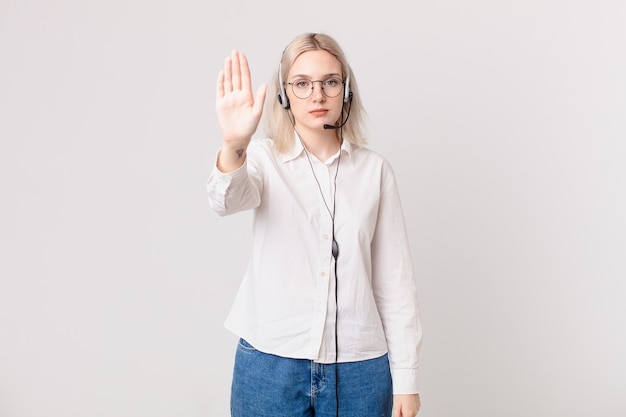 Blond ładna kobieta wygląda poważnie pokazując otwartą dłoń, co gest zatrzymania telemarketing koncepcji
