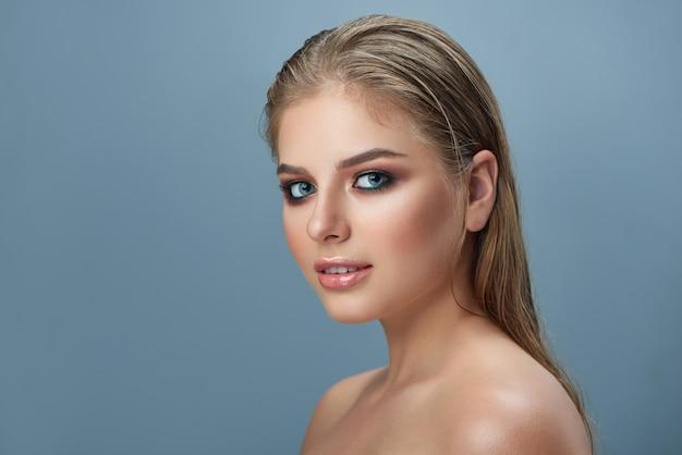 Blond ładna kobieta z profesjonalnym makijażem i długimi włosami.