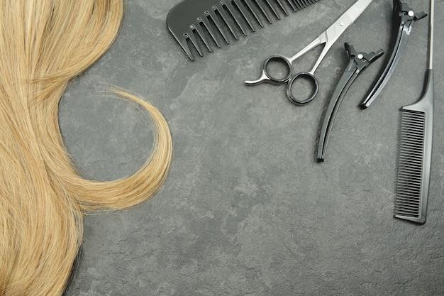 Blond loki i zestaw fryzjerski na szarym tle nożyczki i grzebienie