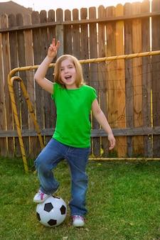 Blond mała dziewczynka gracz piłki nożnej szczęśliwy w podwórku