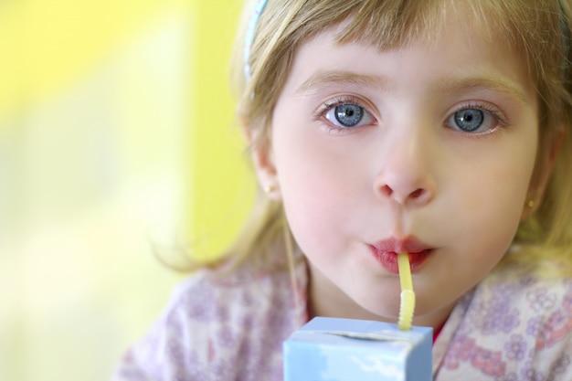 Blond mała dziewczynka pije słomianą tetra cegłę