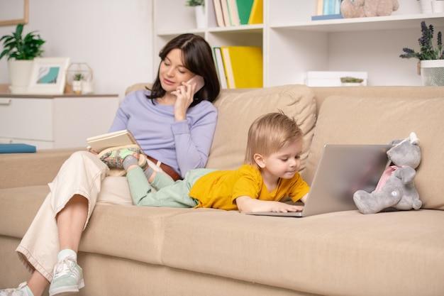 Blond mały chłopiec leży na kanapie przed laptopem i ogląda kreskówki, podczas gdy jego matka rozmawia przez telefon komórkowy i robi notatki w domu