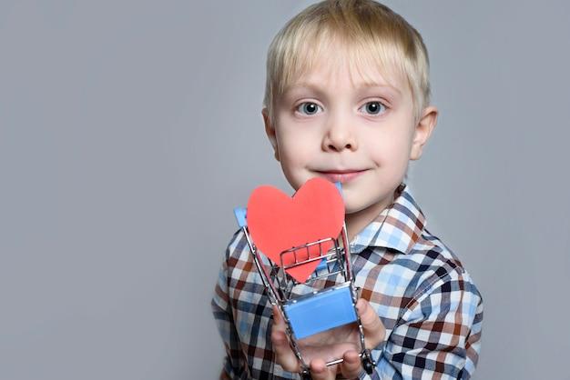 Blond mały chłopiec trzyma metalowy wózek na zakupy z pocztówką w kształcie serca