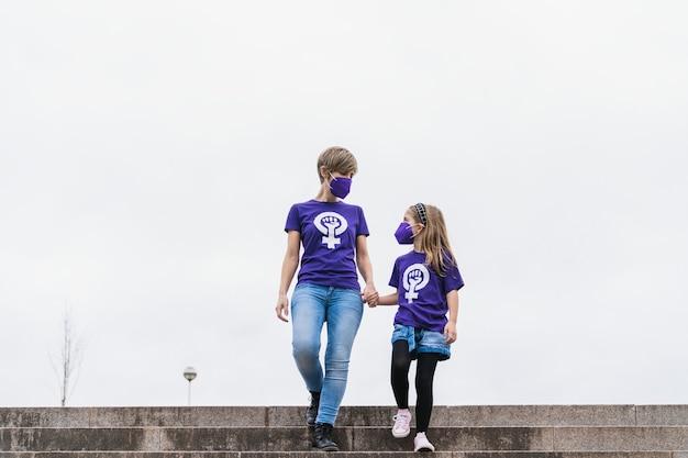 Blond matka i córka idą ulicą w fioletowej koszulce z symbolem pracujących kobiet w międzynarodowy dzień kobiet 8 marca i noszą maskę na pandemię koronawirusa