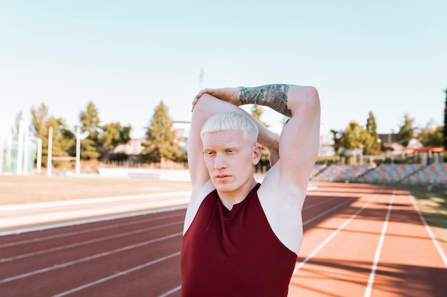 Blond mężczyzna sportowiec rozciągający się na bieżni
