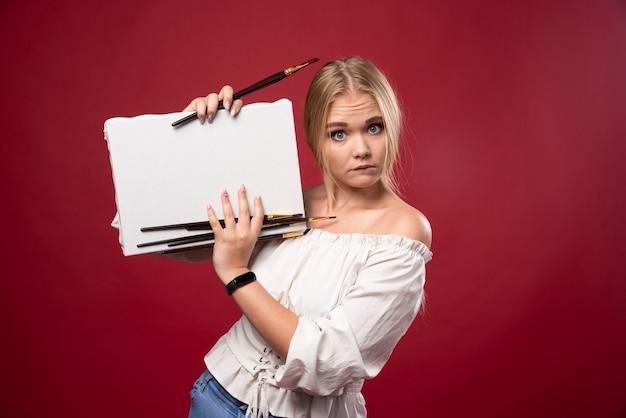 Blond mistrzyni sztuki pracująca na płótnie pędzlem i pokazująca swoje prace z wahaniem.