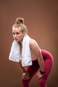 Blond młoda aktywna sportsmenka w różowych leginsach i ręczniku na szyi pochylająca się do przodu podczas przerwy po ciężkim treningu