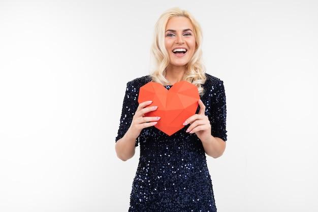 Blond młoda kobieta trzyma papierowego czerwonego serce na bielu z kopii przestrzenią w błękit sukni