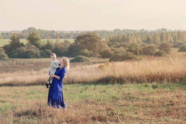 Blond młoda kobieta w niebieskiej sukience w polu o zachodzie słońca