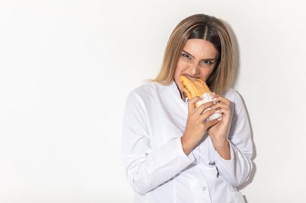 Blond modelka gryzie kanapkę jako wampirzyca i cieszy się.