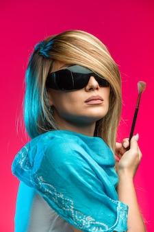 Blond modelka nosi czarne okulary przeciwsłoneczne.