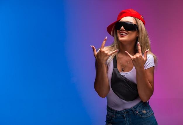 Blond modelka ubrana w sportowe stroje i czarne okulary przeciwsłoneczne.