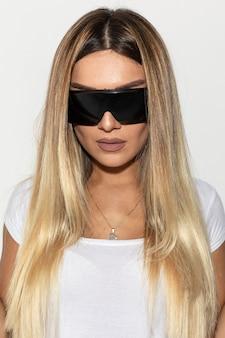 Blond modelka w białej koszuli na sobie czarne okulary przeciwsłoneczne.