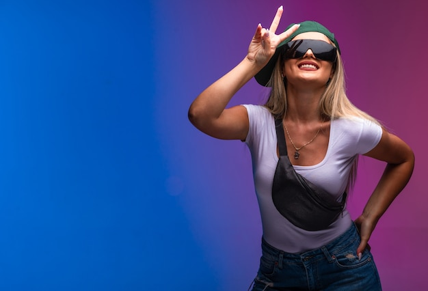 Blond modelka w zielonej czapce i okularach przeciwsłonecznych wysyłająca wiadomość o pokoju.