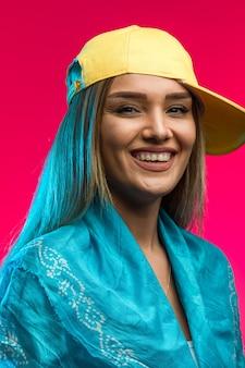 Blond modelka w żółtej czapce prezentuje się pewnie
