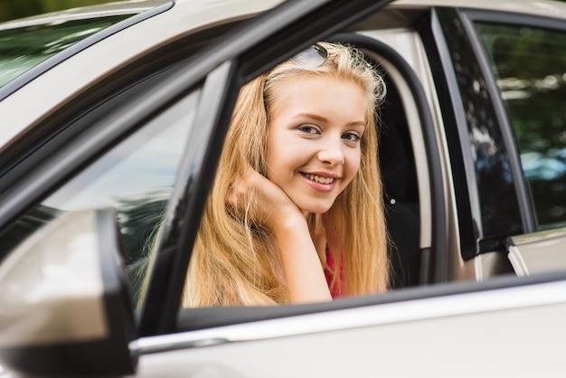 Blond nastolatka siedzi w samochodzie i uśmiecha się