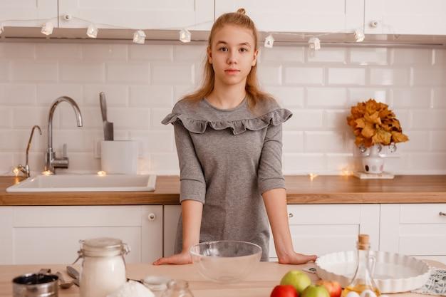 Blond nastolatka w szarej sukience będzie gotować tradycyjną szarlotkę w nowej kuchni