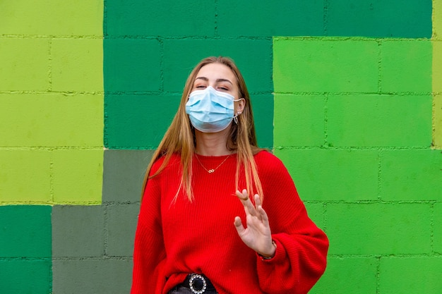 Blond nastolatka z czerwonym swetrem i maską na twarzy uśmiecha się.