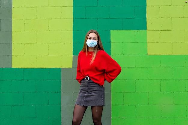 Blond nastolatka z czerwonym swetrem i maską.