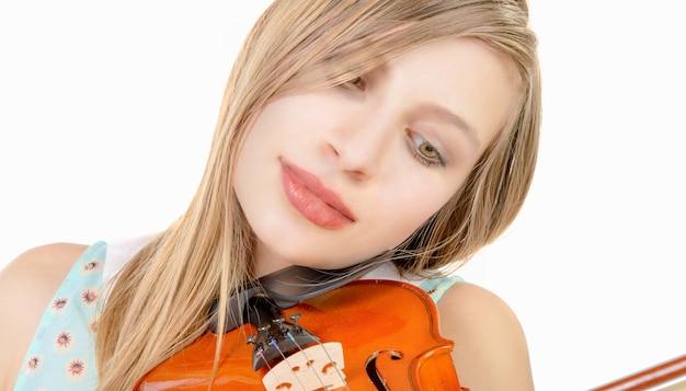 Blond nastolatka z długimi włosami gry na skrzypcach na białym tle