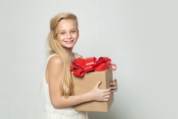 Blond nastolatka z prezentem. wszystkiego najlepszego, dziewczyna z dużym prezentem urodzinowym. cicha sympatia.