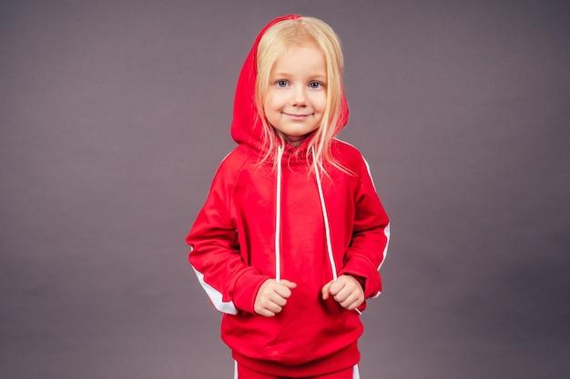 Blond niebieskooka dziewczynka model w czerwonym garniturze sportowym pozowanie w studio na czarnym background.active portret pełnej długości dzieciństwa założyć kaptur na głowę sportowy kostium tancerz hip-hop.