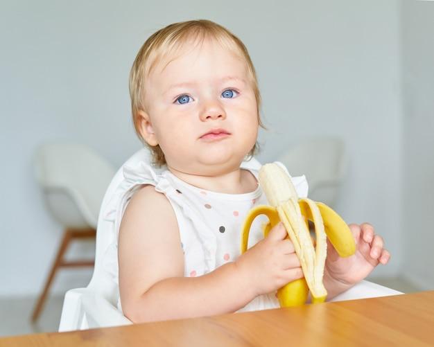 Blond niebieskooki maluch trzyma i gryzie bananową zdrową przekąskę dla najmłodszych