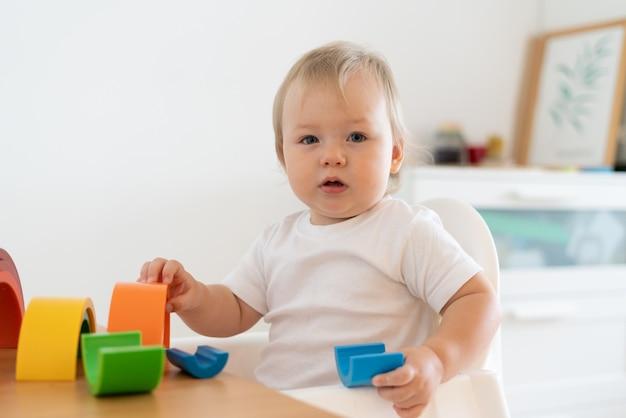 Blond niebieskookie dziecko bawiące się plastikowymi figurami geometrycznymi rozwój motoryczny dziecka w przedszkolu