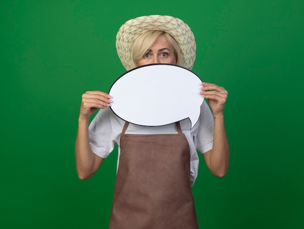 Blond ogrodniczka w średnim wieku w mundurze w kapeluszu trzymająca dymek z tyłu
