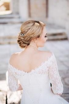 Blond panna młoda z piękną fryzurą i sukienką z odkrytymi ramionami, widok z tyłu