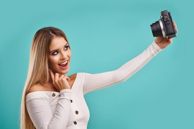 Blond piękna dorosła kobieta pozuje na niebiesko, robiąc natychmiastowe zdjęcia