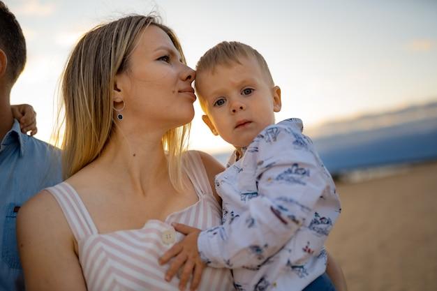 Blond piękna kobieta z synkiem na plaży o zachodzie słońca